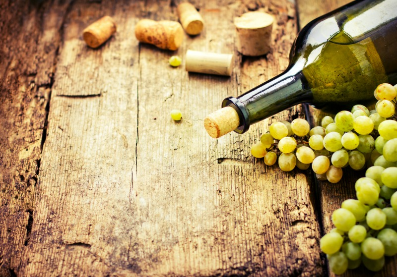 Bottle of wine, grape and corks on wooden table